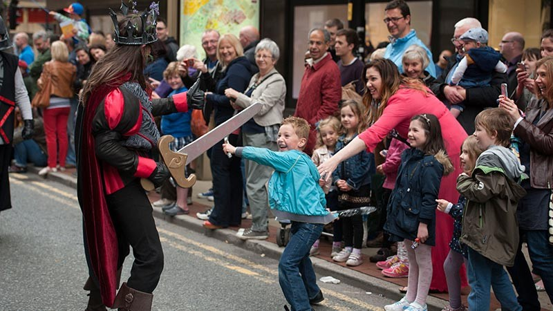 Manchester Day children play-fighting swords with people in parade